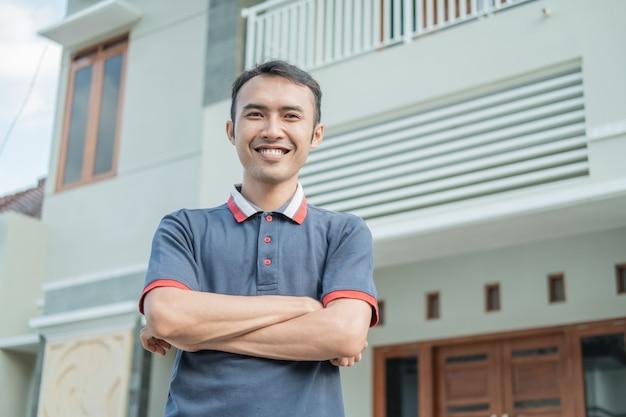 Il maschio asiatico sta con le mani incrociate contro la nuova casa