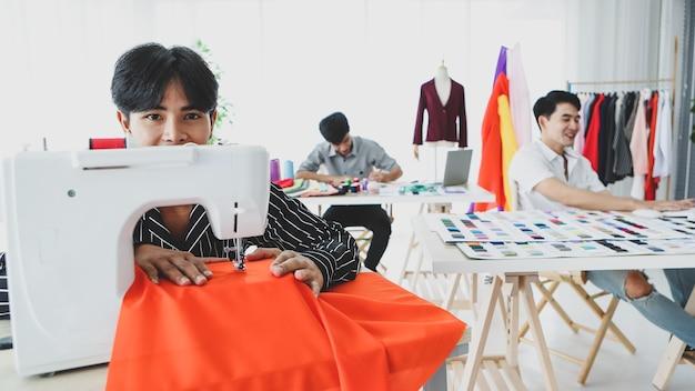 Sarto maschio asiatico che usa la macchina da cucire vicino ai colleghi con campioni di stoffa mentre lavorano insieme in studio