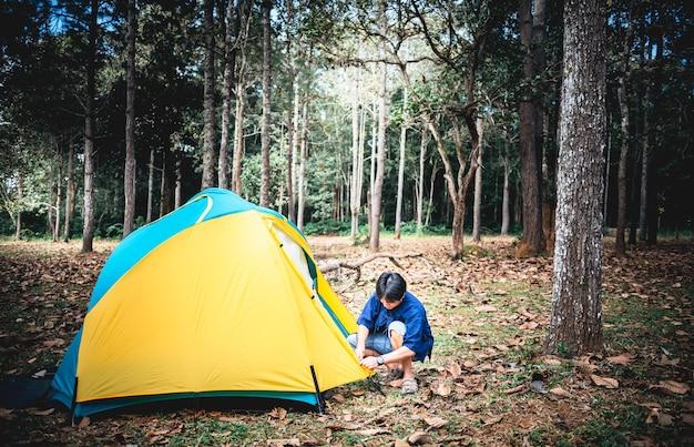 Un turista maschio asiatico, lancia una tenda gialla per il campeggio in una foresta con alberi ad alto fusto, alle persone e al concetto di viaggio.