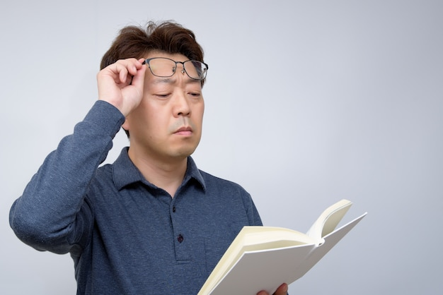 Maschio asiatico che prova a leggere qualcosa nel suo libro. vista scarsa, presbiopia, miopia.