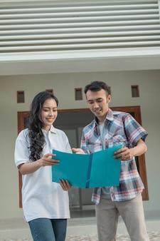Maschio asiatico con gesto della mano in chat con lo sviluppatore immobiliare mentre esplora la nuova casa