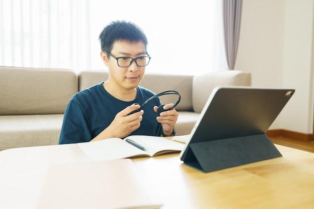 Uomo asiatico di età compresa tra 30 e 40 anni utilizzando tablet, guardando lezione corso online comunicare b