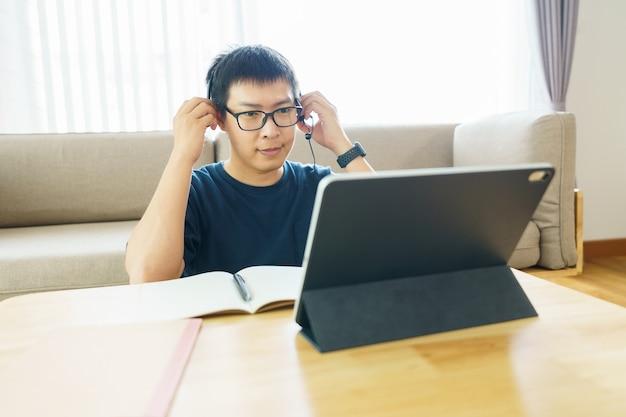 Uomo asiatico di età compresa tra 30 e 40 anni utilizzando tablet, guardando lezione corso online comunicare