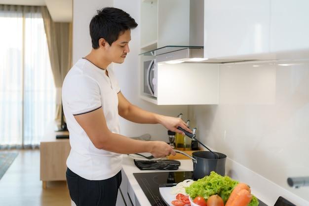 L'uomo asiatico sta usando un mestolo per addensare la zuppa di verdure in una pentola nella cucina di casa.