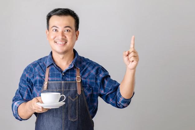 Uomo asiatico in uniforme da barista che tiene tazza di caffè
