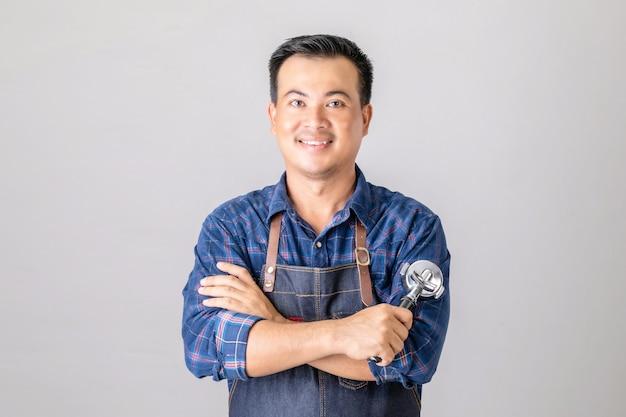 Uomo asiatico in uniforme da barista che tiene macchina da caffè attrezzo