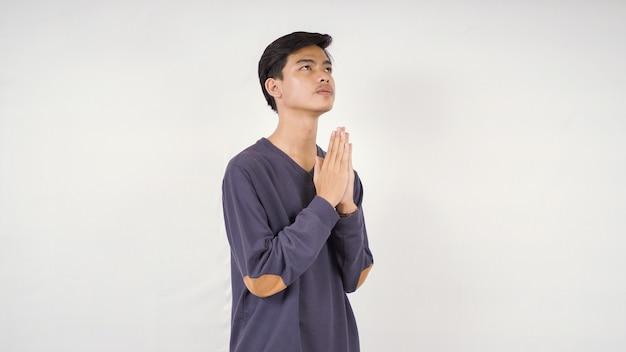 Uomo asiatico che implora speranza isolato su sfondo bianco