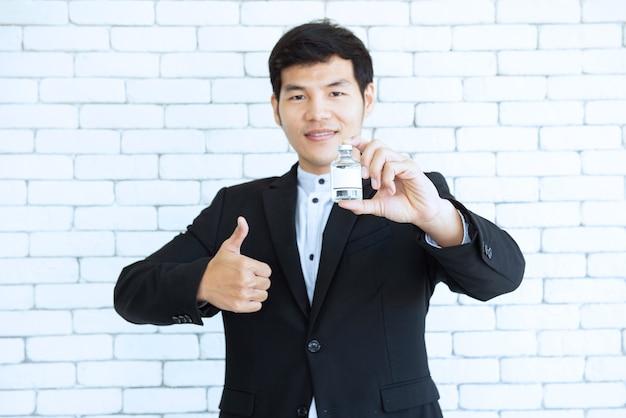 Uomo asiatico in vestito nero tenere in mano la fiala di vaccino con thrump