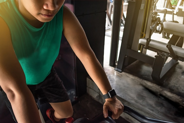 Il culturista asiatico dell'uomo con la macchina della bicicletta pesa il potere bello Foto Premium