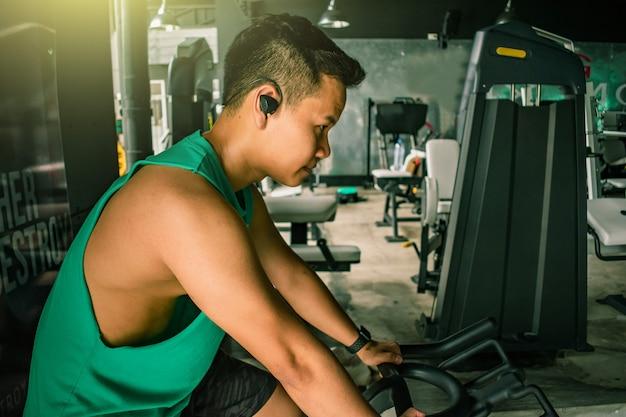 Il culturista asiatico dell'uomo con la macchina della bicicletta pesa il potere bello