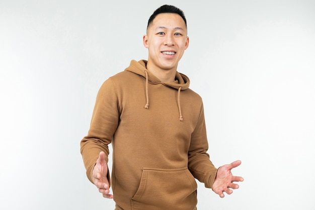 Uomo asiatico in maglia con cappuccio marrone a braccia aperte su un bianco