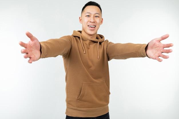 Uomo asiatico in felpa con cappuccio marrone con le braccia aperte