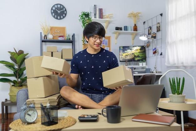 Imprenditore uomo asiatico o vendita di merci online e preparare la scatola dei pacchi di cartone di imballaggio del prodotto