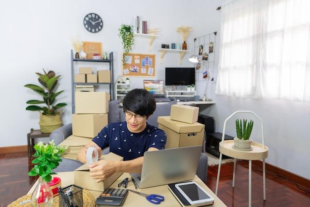 Imprenditore uomo asiatico o vendita di merchance online e prepara il prodotto
