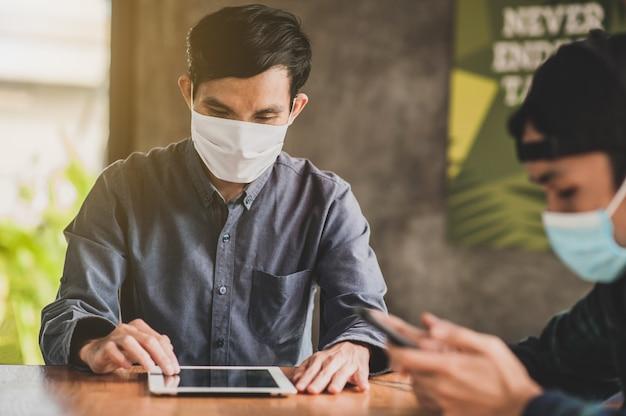Maschera per il viso asiatica di uso professionale dell'uomo d'affari che si siede nel nuovo stile di vita sociale normale del caffè dopo il blocco del virus della corona