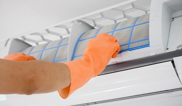 Uomo asiatico che pulisce il filtro sporco del condizionatore d'aria