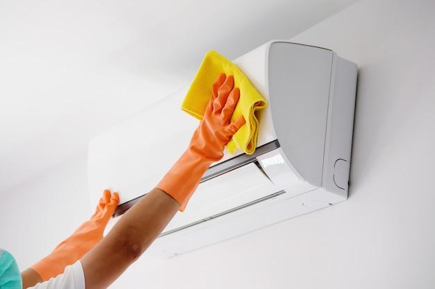 Uomo asiatico che pulisce il condizionatore d'aria con un panno in microfibra