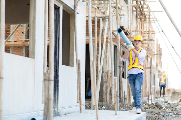 Operaio edile uomo asiatico tenendo il tubo e lavorando in loco.