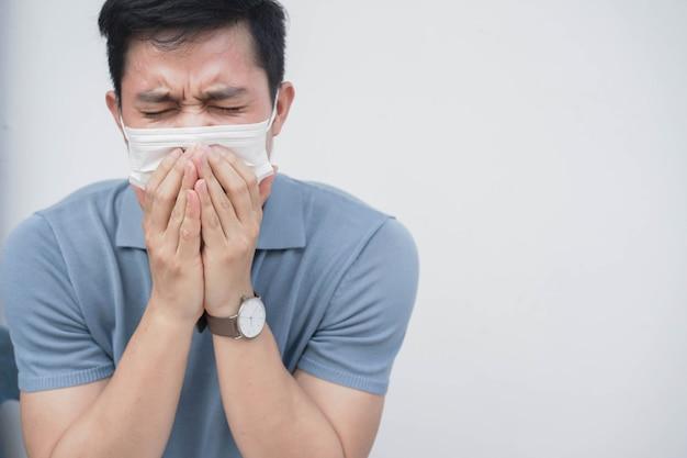 Uomo asiatico che tossisce dentro la maschera di protezione dopo avere respirato l'area di quarantena per il concetto di coronavirus