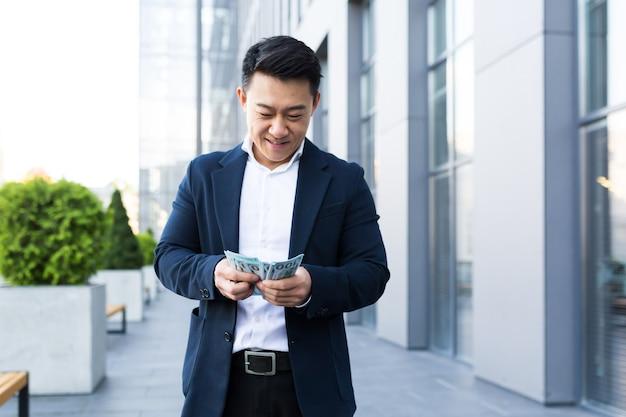 L'uomo asiatico conta i soldi vicino all'ufficio, l'uomo d'affari felice ha un sacco di soldi