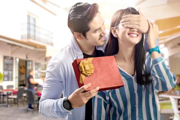 Uomo asiatico che copre gli occhi della sua ragazza e dandogli confezione regalo