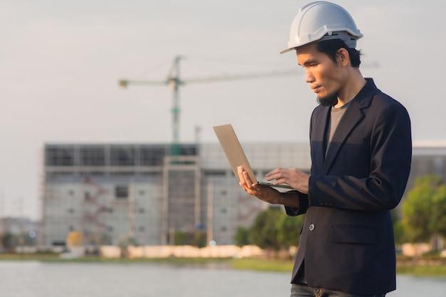 Il progettista asiatico dell'uomo lavora all'aperto nella pianta della fabbrica della costruzione del sito della zona