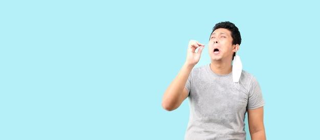 L'uomo asiatico fa un autotest per covid 19 su sfondo blu