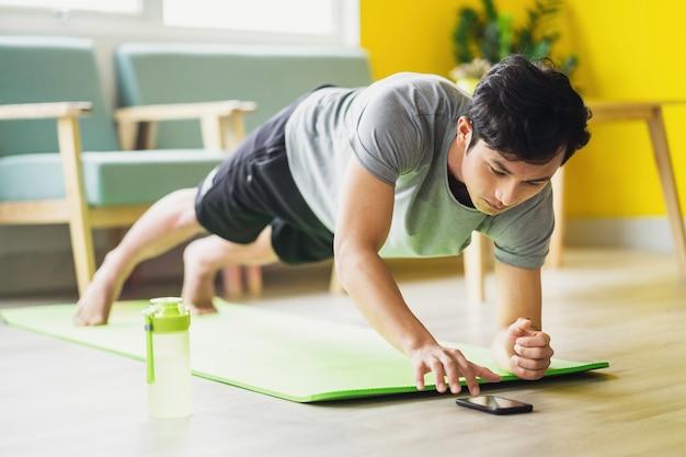 Uomo asiatico che fa esercizio a casa