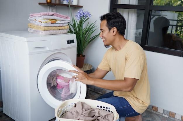 Uomo asiatico che fa il bucato a casa caricamento di vestiti in lavatrice