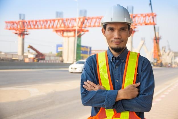 Il lavoratore asiatico dell'ingegnere dell'uomo che sta sulla costruzione del sito, elmetto di architettura protegge il controllo dell'operaio