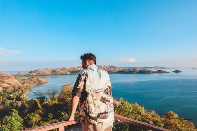 Uomo asiatico che gode della vista dell'oceano con le colline dal balcone a labuan bajo
