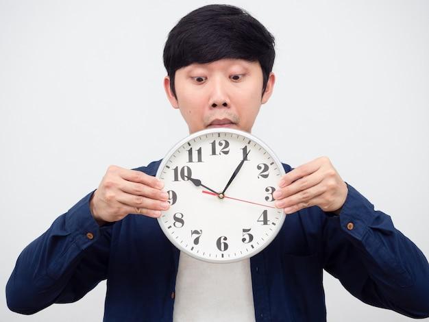 Uomo asiatico entusiasta di guardare l'orologio nel suo ritratto in mano, concetto tardivo