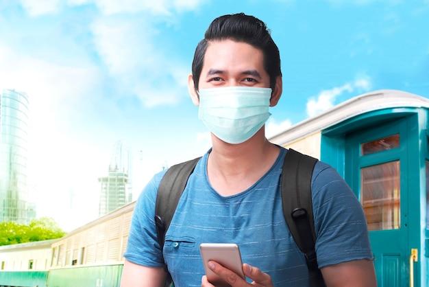 Uomo asiatico nella maschera facciale con uno zaino che tiene lo smartphone sulla stazione ferroviaria. in viaggio nella nuova normalità