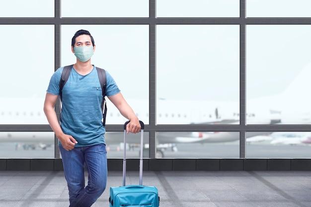 Uomo asiatico nella maschera facciale con zaino e valigia sul terminal dell'aeroporto. in viaggio nella nuova normalità