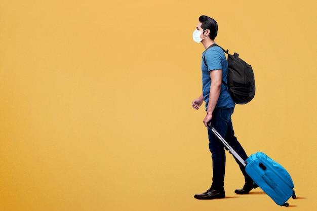 Uomo asiatico nella maschera facciale con zaino e valigia. viaggiare nella nuova normalità