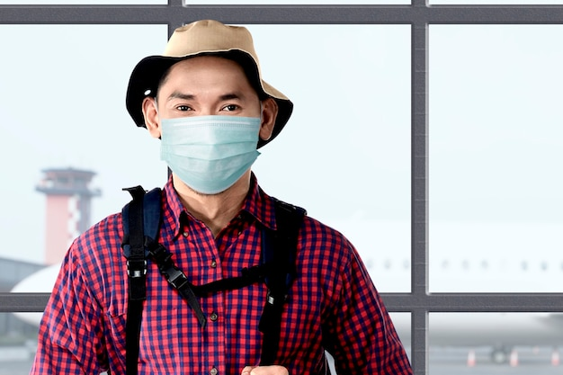 Uomo asiatico con la maschera per il viso con cappello e zaino sul terminal dell'aeroporto. viaggiare nella nuova normalità