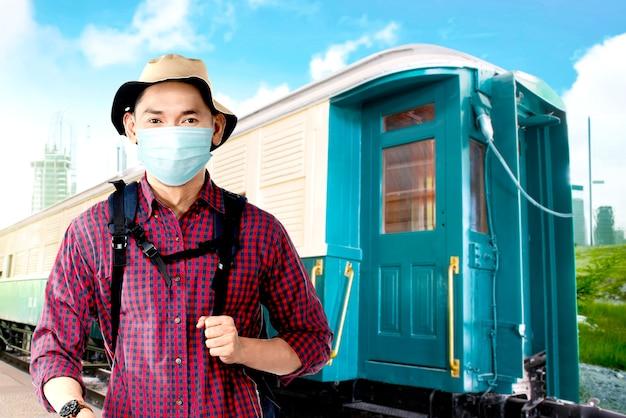 Uomo asiatico nella maschera facciale con cappello e zaino sulla stazione ferroviaria. in viaggio nella nuova normalità