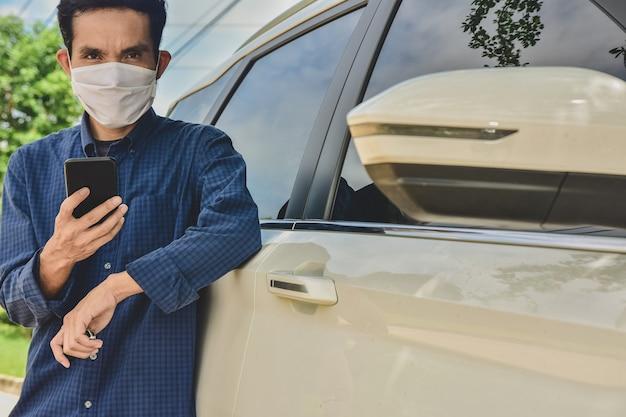 Uomo asiatico in maschera facciale tenendo il telefono in piedi in macchina