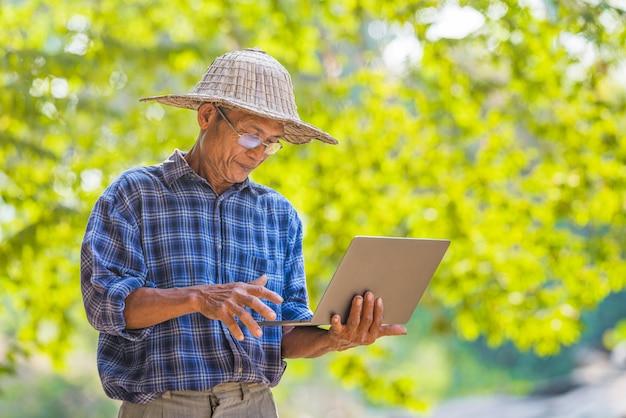 Coltivatore asiatico dell'uomo con il concetto di affari e tecnologia del computer portatile e dello smart phone, agricoltore asiatico dell'uomo sullo spazio vuoto della copia