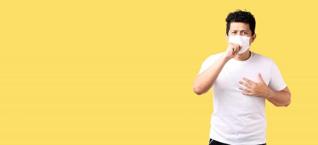L'uomo asiatico sente dolore ai polmoni e indossa l'inquinamento da maschera protettiva o malattie infettive trasmissibili e coronavirus o concetto covid-19, assistenza sanitaria e malattia su sfondo giallo in studio per annunci.
