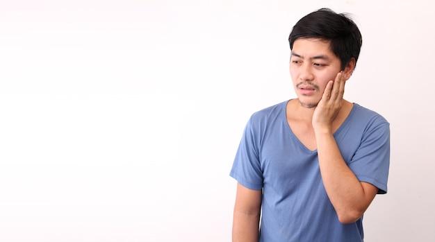 Uomo asiatico che sente dolore, tenendo la guancia con la mano, soffre di mal di denti.