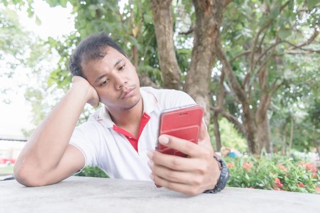 L'uomo asiatico sente il momento annoiato e triste con il telefono cellulare. aspetta qualcosa dal cellulare.