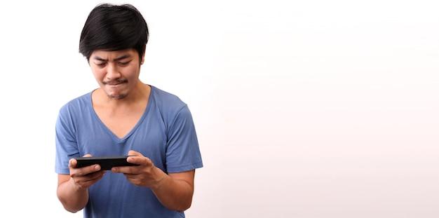 Uomo asiatico divertente dedito al gioco per cellulare su sfondo bianco.