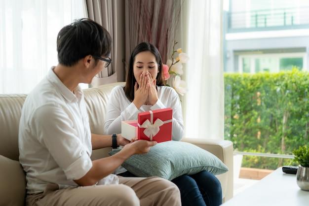 L'uomo asiatico dà ad una donna un contenitore di regalo rosso. guarda il regalo nella confezione e sorprende per l'anniversario di matrimonio o il suo compleanno nel salotto di casa.