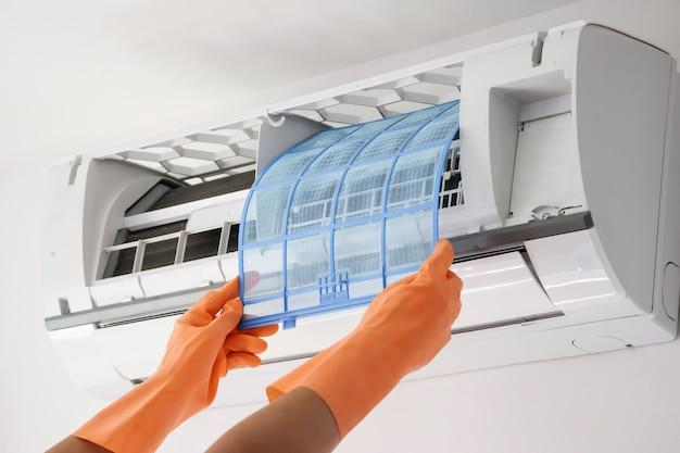 Uomo asiatico tenere in mano il concetto di pulizia del filtro del condizionatore d'aria