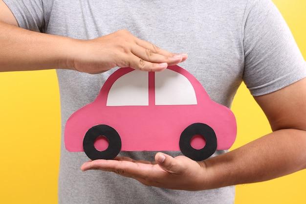 Forma di automobile di carta rossa della stretta della mano dell'uomo asiatico su fondo giallo in studio. protezione del concetto di auto.