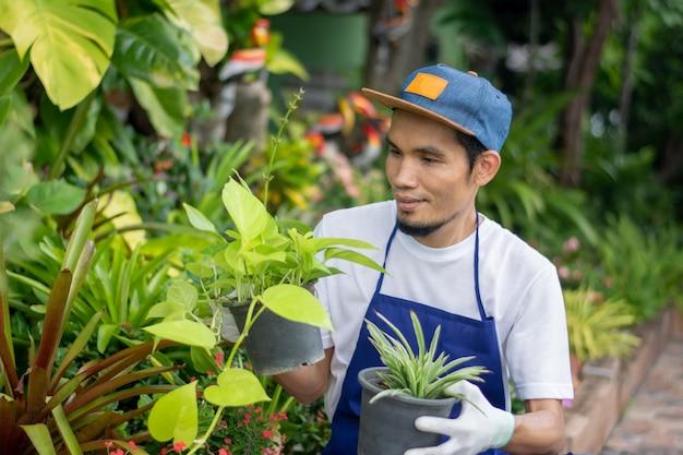 L'uomo asiatico vende felice il giardino delle piante in negozio
