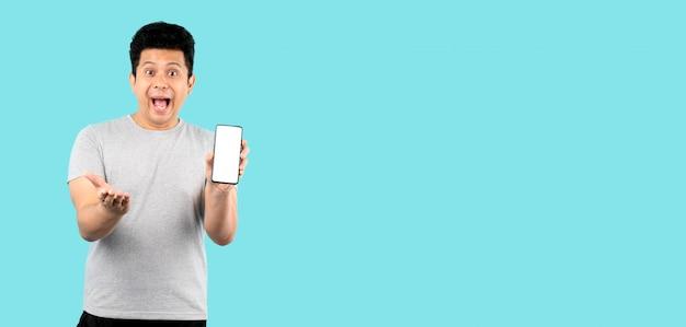 Sorridere felice dell'uomo asiatico sulla parete blu, presentando smart phone e indicando con il dito allo schermo bianco in bianco