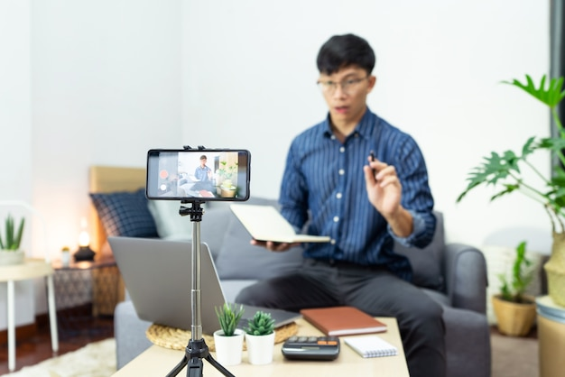 Uomo asiatico in cuffie che scrive note nel taccuino che guarda gli studi del corso di video del webinar tramite laptop a casa studio in linea, concetto di e-learning.