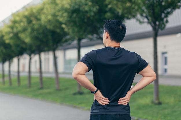 Uomo asiatico che trattiene il dolore alla schiena dopo la corsa e il fitness
